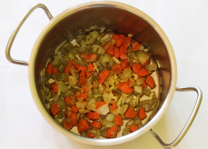 κρεμμύδι, καρότο, σκ'ορδο, και τριμμένο τζίντζερ στην κατσαρόλα
